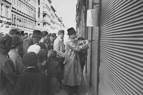 """<p>Onlookers watch as a Jewish man is forced to paint anti-Jewish graffiti on a shuttered storefront. <a href=""""/narrative/6000/en"""">Vienna</a>, Austria, March 1938.</p>"""