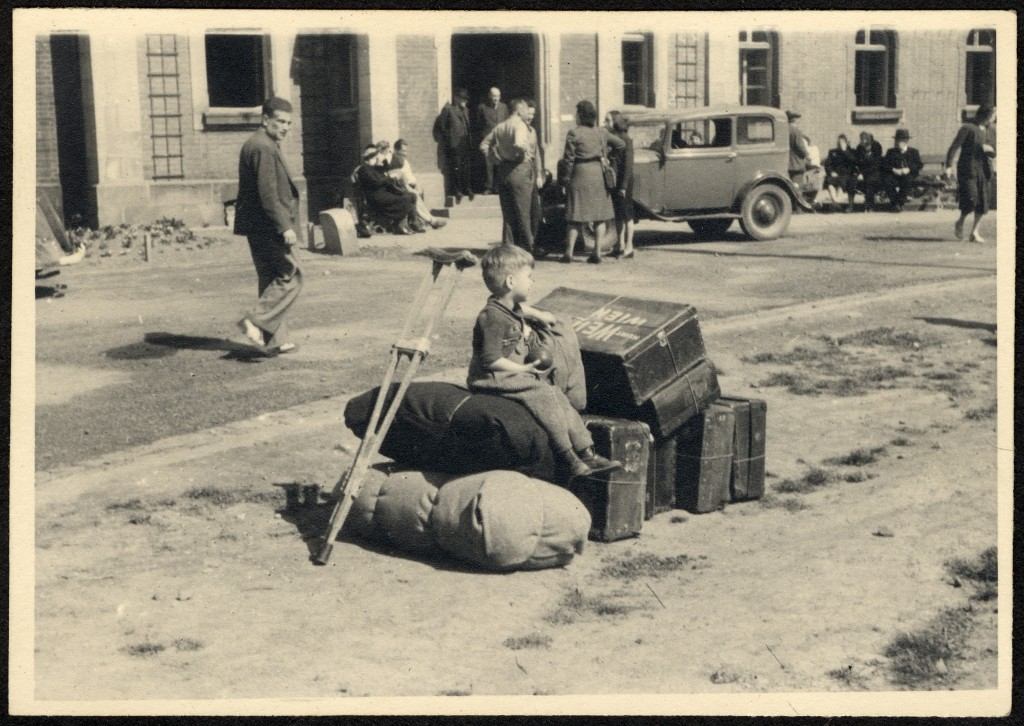 "<p>A young child sits among luggage while waiting to depart the <a href=""/narrative/11676/en"">Deggendorf</a> displaced persons camp. Deggendorf, Germany, 1945-46.</p>"