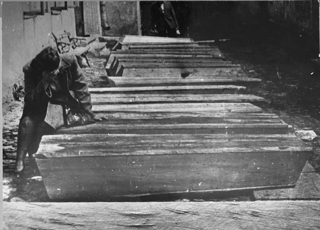 A woman mourns by the coffins of Jews who died in the Kielce pogrom. [LCID: 63688a]