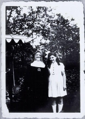 "<p>Augusta Feldhorn stands next to a nun while in hiding. Augusta, a Jewish child, was in <a href=""/narrative/7723/en"">hiding under an assumed Christian identity</a>. Belgium. 1942-1945.</p>"
