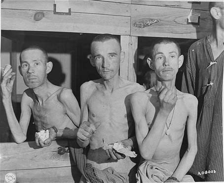 "<p>Emaciated survivors in the <a href=""/narrative/28379"">Ebensee</a> subcamp of the Mauthausen concentration camp suck on sugar cubes provided by US soldiers upon the liberation of the camp. Photograph taken by Signal Corps photographer <a href=""/narrative/8148"">J Malan Heslop</a>. Ebensee, Austria, May 8, 1945.</p>"