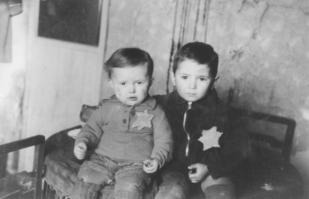 <p>شقيقان صغيرا السن، يجلسان لالتقاط صورة عائلية في حي اليهود في كوفنو. وبعد ذلك بشهر، تم ترحيلهما إلى محتشد مايدانيك. كوفنو، ليتوانيا، شباط/فبراير عام 1944.</p>