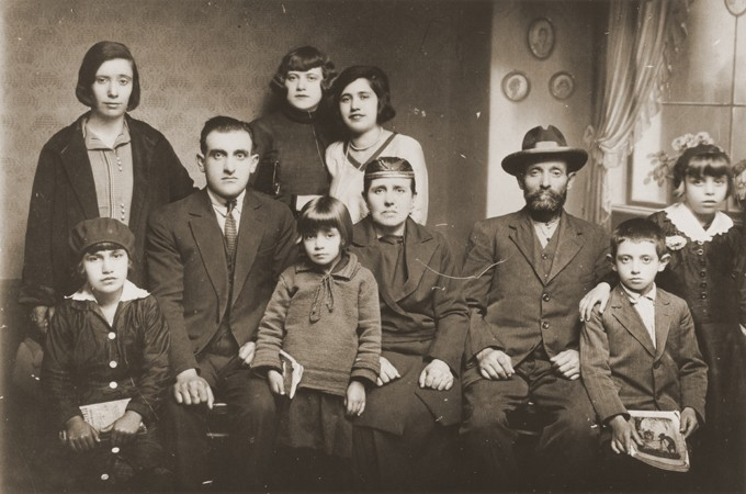 """<p>Portrait of the family of Mushon and Rebeka Kamchi in Bitola. Isak Kamchi is pictured in the front row at the right. Isak was born in Bitola. Several of his siblings and cousins left Macedonia for Palestine and North America before the war. During World War II, Isak served as the leader of a partisan unit operating in Croatia. He established a safehouse at his parent's home in Zagreb where partisans could rest and recuperate. His mother ran the safehouse, cooking for the men and nursing them back to health. When the Germans discovered the safehouse, they offered Isak protection in exchange for his surrender. However, when he did surrender, he was arrested and later killed. He may have been publicly hanged. Photograph taken in <a href=""""/narrative/9092"""">Bitola</a>, ca. 1932.</p>"""