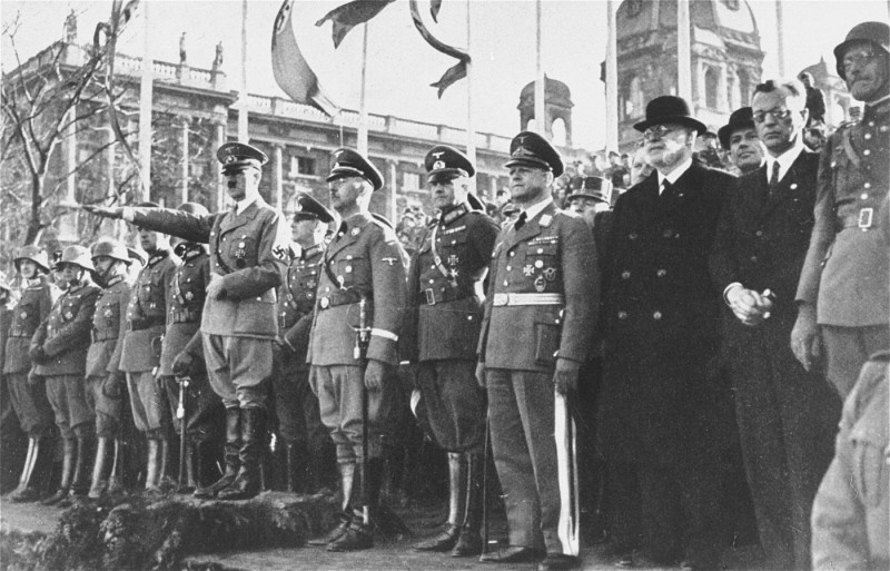 "<p>Adolf Hitler and his entourage view a military parade following the annexation of <a href=""/narrative/5815"">Austria</a> (the <em>Anschluss</em>). Vienna, Austria, March 1938.</p>"