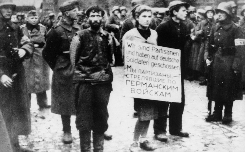 "<p>German soldiers parade three young people through Minsk before their execution. The placard reads: ""We are partisans who shot at Germans soldiers."" Minsk, Soviet Union, October 26, 1941.</p>"