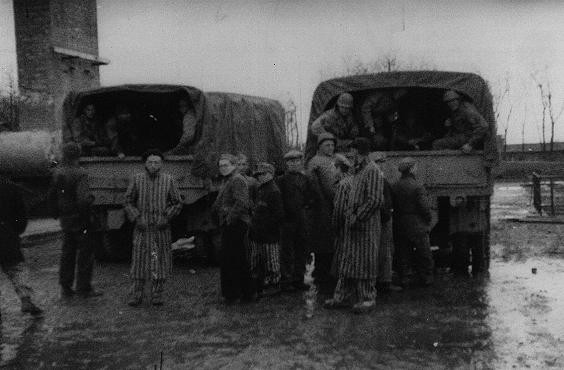 Survivors of the Buchenwald concentration camp gather around trucks carrying American troops. [LCID: 04064]