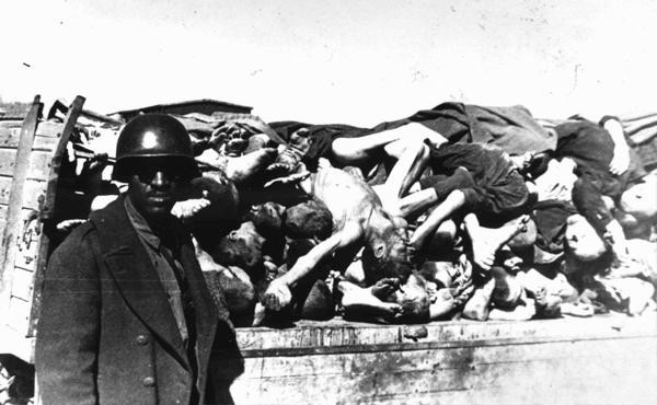 An American soldier on an inspection tour of Buchenwald poses for a photograph beside a wagon laden with corpses. [LCID: 85276]