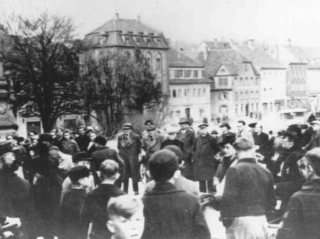 <p>یهودیان در شهر کیتسینگن آلمان، واقع در شمال غربی مونیخ، برای تبعید شدن جمع شده اند. کیتسینگن، آلمان، مارس 1942.</p>