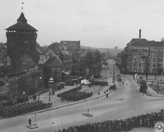 The inhabitants of Nuremberg watch a parade of US troops through their city. [LCID: 34618]