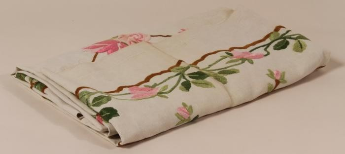 Tablecloth with roses embroidered by her mother carried by 17 year old Hannah Kronheim when she left Germany on the Kinderstransport [Children's Transport] in 1939.