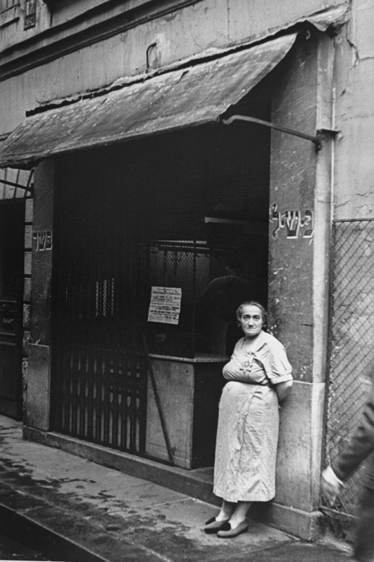 In the Jewish quarter of Paris, a Jewish woman wearing the compulsory Jewish badge stands at the entrance to a kosher butcher shop. [LCID: 81042]