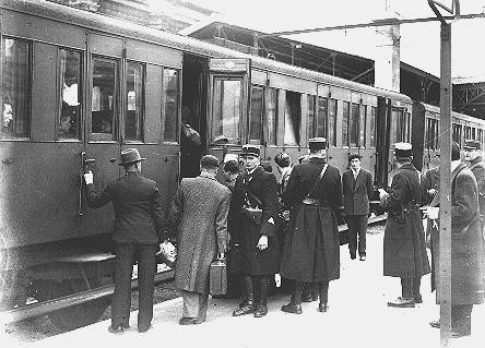 """<p>Jewish deportees, guarded by French police, board a train at the Austerlitz station for transport to the Pithiviers internment camp. <a href=""""/narrative/6033/en"""">Paris</a>, France, May 1941.</p>"""