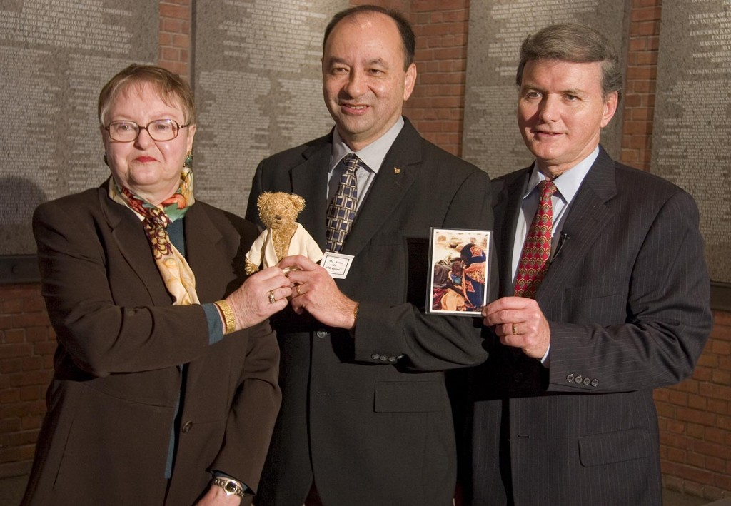 """<p>Dr. <a href=""""/narrative/9190"""">Sophie Turner-Zaretsky</a>, Space Shuttle Discovery Commander Mark Polansky, and United States Holocaust Memorial Museum chief of staff Bill Parsons. They are holding a replica of """"Refugee"""" bear and a photo of a Darfurian child refugee, items taken by Commander Polansky on a December 2006 Space Shuttle mission.</p>"""