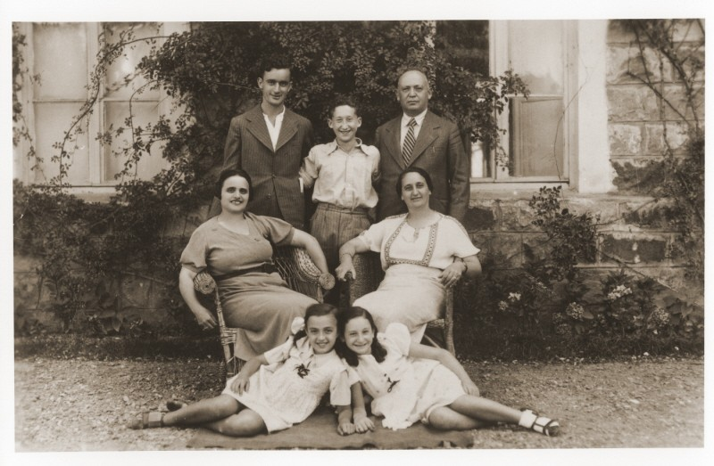 """<p>Members of the Amarillo family pose outside their home in <a href=""""/narrative/5364/en"""">Salonika</a>. Front, from left to right, are Tillie Amarillo and Sarika Yahiel. Seated behind them are their mothers Louisa Bourla Amarillo and Regina Amarillo Yahiel. Standing are Saul Amarillo, Isaccino Yahiel, and Isaac Yahiel. Salonika, <a href=""""/narrative/4964/en"""">Greece</a>, between 1930 and 1939.</p>"""