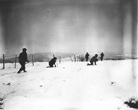<p>John Perry, a movie photographer with Unit 129, films GIs of the 290th Infantry Regiment, 75th Infantry Division, and 4th Cavalry Group ferreting out German snipers near Beffe, Belgium during the Battle of the Bulge. Twelve Germans were killed. The scene was photographed by Carmen Corrado of the 129th. January 7, 1945. US Army Signal Corps photograph taken by C.A. Corrado.</p>