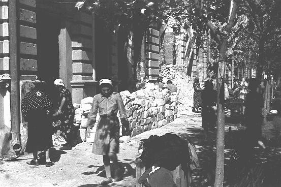<p>Jewish women at forced labor in the process of clearing rubble from the main street. Kishinev, Bessarabia, Romania, August 12, 1941.</p>