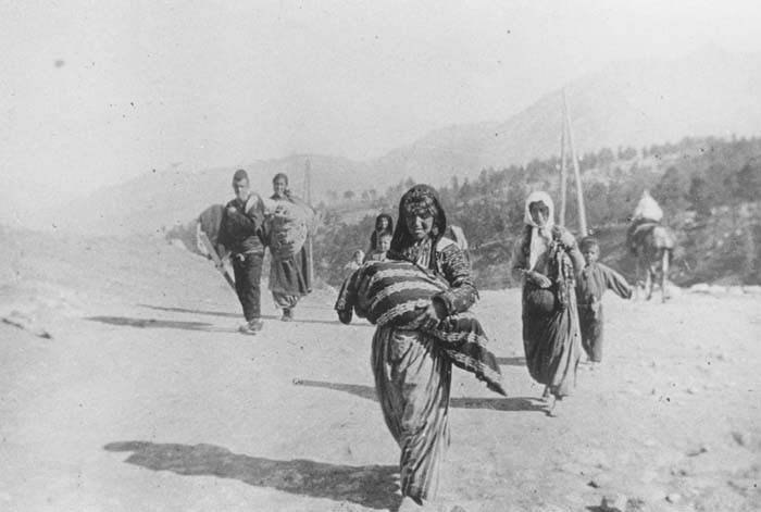 A small group of Armenian deportees walking through the Taurus Mountain region, carrying bundles. [LCID: 94418]
