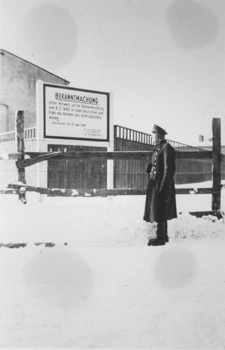 """A member of the German Order Police Battalion 101 stands next to a sign marking the entrance to the Lodz ghetto in German-occupied Poland, 1940–1941. The German text of the sign, reads: """"Announcement: In accordance with a police order of February 8, 1940, all Germans and Poles are forbidden entry into the ghetto area."""""""