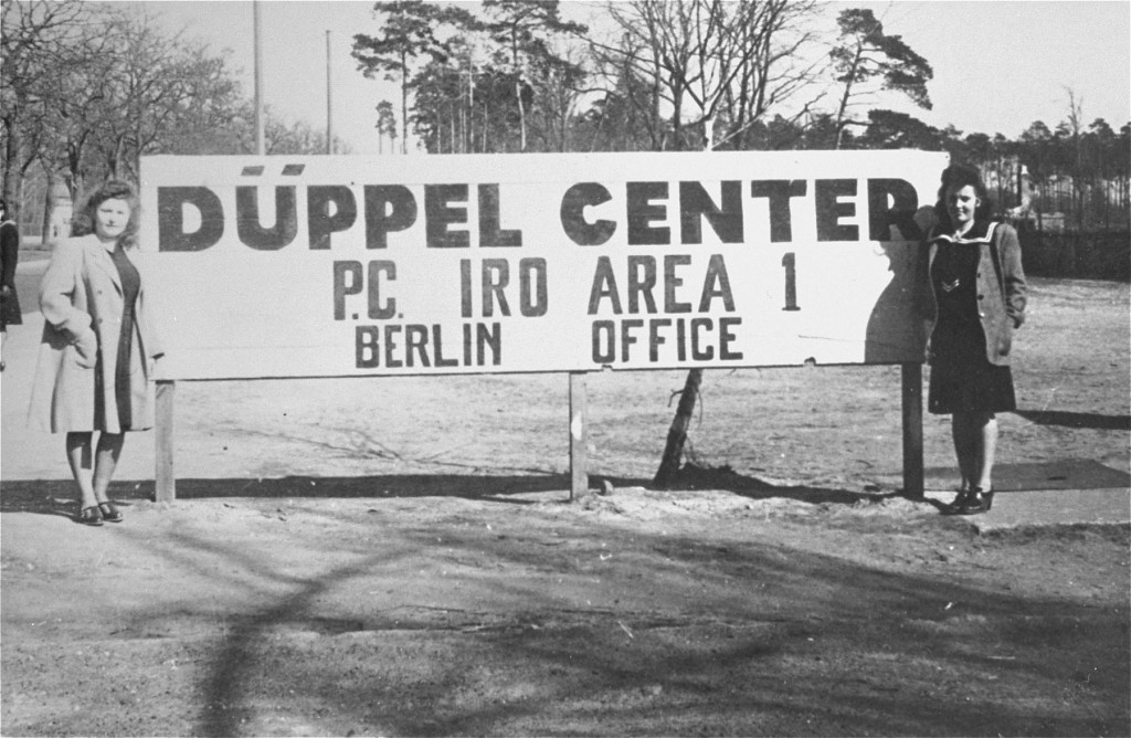"<p>Displaced persons (DPs), Lusia Gliklich (left) and Andzia Dell, stand beside the sign in front of the <a href=""/narrative/53465/en"">Düppel Center</a> DP camp, also called Schlachtensee.</p>"