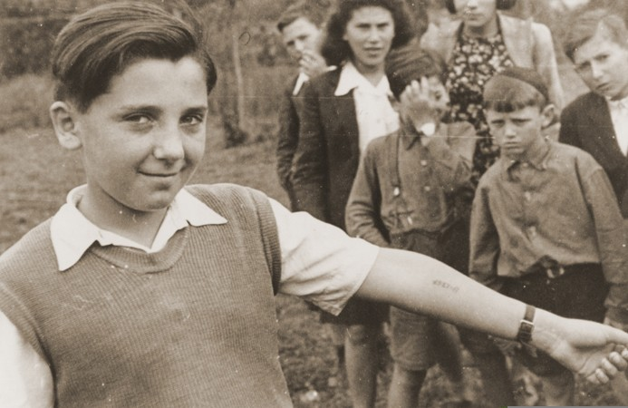 <p>At the Neu Freimann displaced persons camp, a boy displays the tattooed number on his arm to a photographer.  Other children  look on. Neu Freimann, Munich, Germany, between 1945 and 1949.</p>