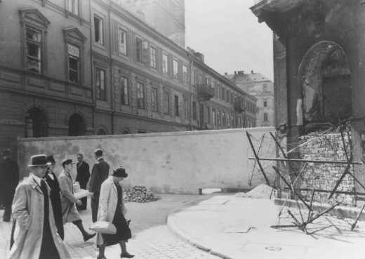 Polish civilians walk by a section of the wall that separated the Warsaw ghetto from the rest of the city. [LCID: 78390]
