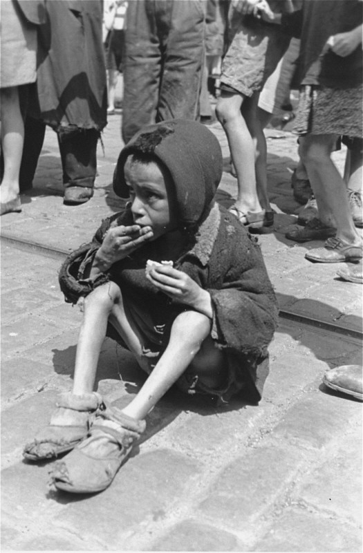 An emaciated child eats in the streets of the Warsaw ghetto. [LCID: 89469]