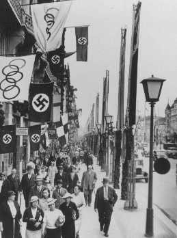 A street scene showing displays of the Olympic and German (swastika) flags in Berlin, site of the summer Olympic Games. [LCID: 76499]
