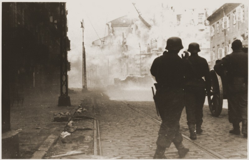 German soldiers direct artillery against a pocket of resistance during the Warsaw ghetto uprising. [LCID: 34083b]