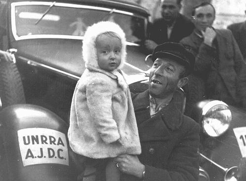 <p>Personnes déplacées juives de Pologne dans un camp de l'UNRRA (Administration des Nations Unies pour les secours et la reconstruction). Le signe sur la voiture indique que le Joint (American Joint Distribution Committee, organisation caritative juive américaine) était actif dans ce camp. Babenhausen, Allemagne, vers 1946.</p>