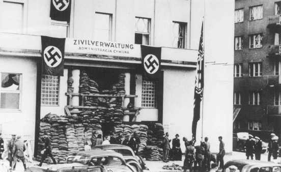 Invading German soldiers raise the Nazi flag in front of the city hall.