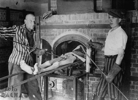 Survivors of the Dachau concentration camp demonstrate the operation of the crematorium by pushing a corpse into one of the ovens. [LCID: 15026]