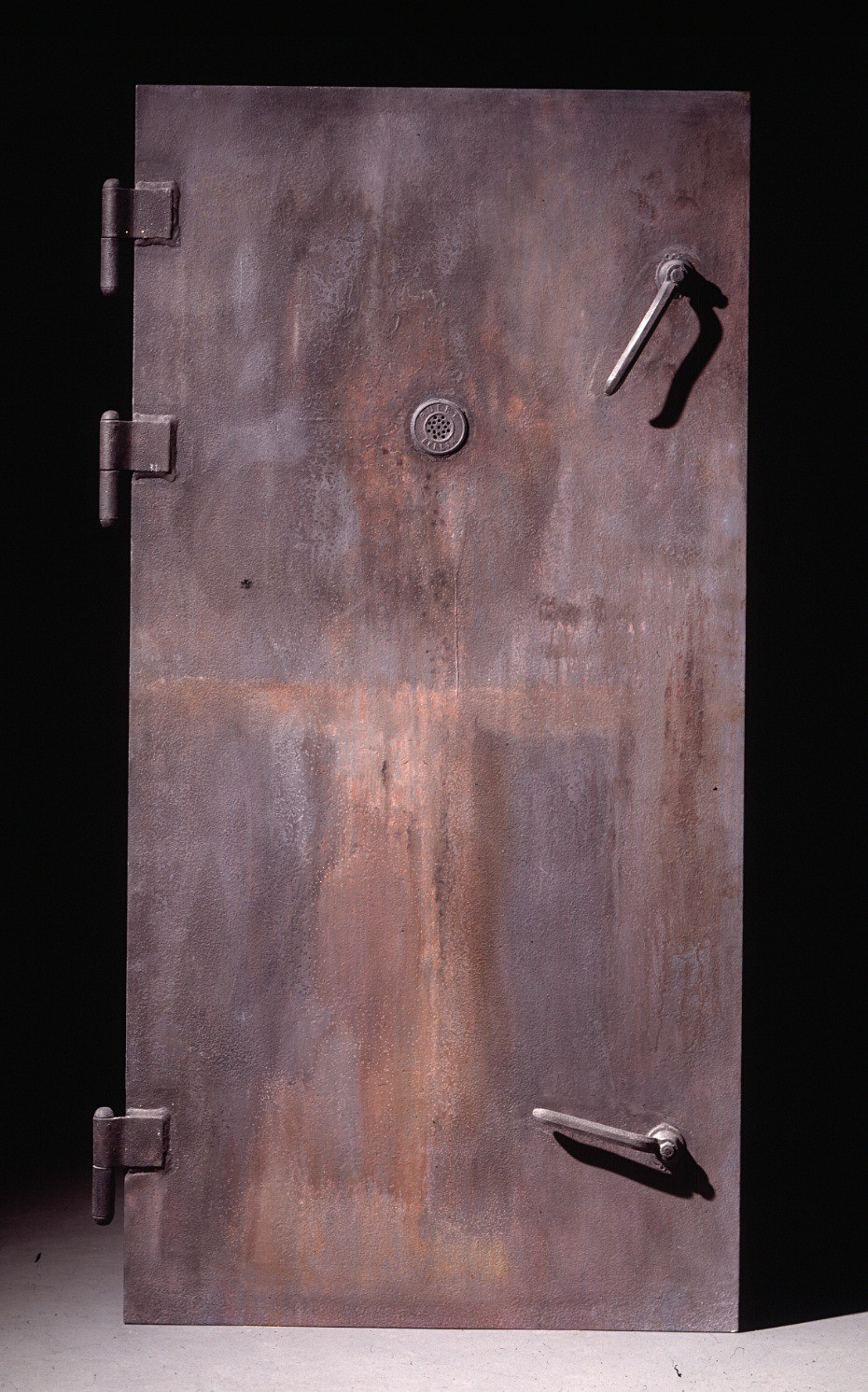 """<p>This casting of a gas chamber door in the <a href=""""/narrative/3168/en"""">Majdanek</a> camp, near Lublin, Poland, was commissioned by the United States Holocaust Memorial Museum. Each gas chamber in Majdanek was fitted with an airtight metal door and was bolted shut before gas entered the chamber inside. SS guards could observe the killing process through peepholes in the upper center of the door.</p>"""