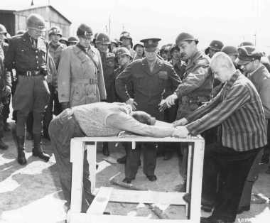 """<p>A survivor shows US Generals Eisenhower, Patton, and Bradley how inmates at the <a href=""""/narrative/7757/en"""">Ohrdruf</a> camp were tortured. Ohrdruf, Germany, April 1945.</p>"""