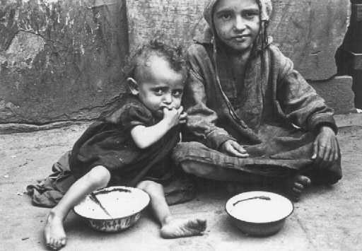 <p>Children eating in a Warsaw ghetto street. Warsaw, Poland, between 1940 and 1943.</p>