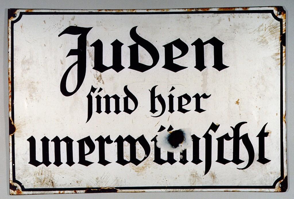 """<p>Подобные знаки, воспрещающие вход евреям, вывешивались в общественных местах (парках, театрах, кинотеатрах, ресторанах) по всей нацистской Германии. На этом знаке написано по-немецки: """"Евреи здесь нежелательны"""".</p>"""