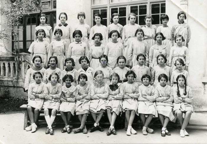 <p>A group of Tunisian schoolgirls wearing aprons. Nadia Cohen is in the first row, third from the left. Tunis, Tunisia, ca. 1930-1935.</p>