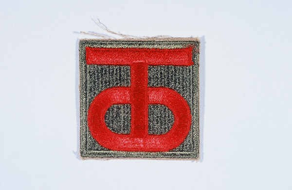 """Insignia of the 90th Infantry Division. Called the """"Tough Ombres,"""" the 90th Infantry Division was raised from draftees from the states ... [LCID: n05649]"""