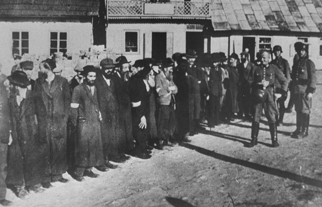 """<p>Members of the German Order Police stand guard over a group of Orthodox Jewish men, 1942. The men have been rounded-up either for <a href=""""/narrative/3384"""">forced labor</a> or <a href=""""/narrative/55010"""">public humiliation</a>. Krakow, in German-occupied <a href=""""/narrative/2103"""">Poland</a>.</p>"""