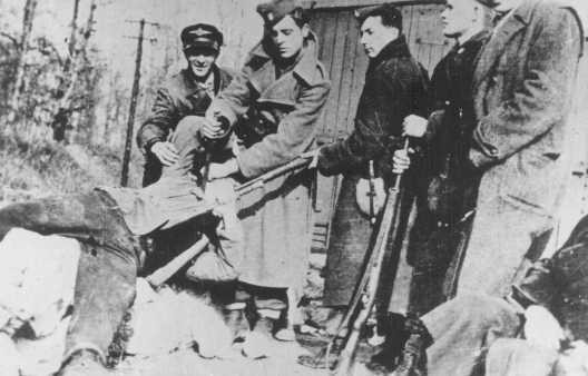 <p>Ustasa (Croatian fascist) soldiers prepare to kill a victim with a dagger and bayonet. Yugoslavia, between 1941 and 1944.</p>