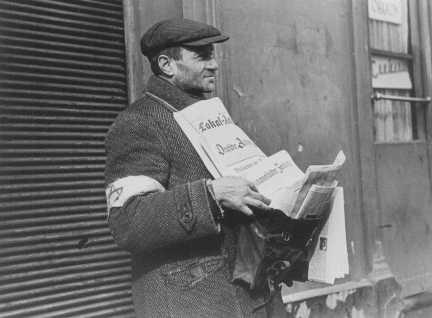 <p>A Jewish street vendor, wearing the compulsory armband, sells German-language newspapers. Warsaw ghetto, Poland, February 1941.</p>