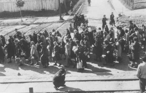 <p>Ghetto photographer Mendel Grossman (foreground) takes photos of a deportation. Lodz ghetto, Poland, June-August 1944.</p>