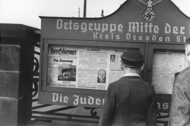 "<p>German boys read an issue of <em>Der Stuermer</em> newspaper posted in a display box at the entrance to a Nazi Party headquarters in the Dresden region. The German slogan (partially obscured) at the bottom of the display box reads, ""The Jews are our misfortune.""</p>"