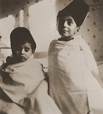 """<p>Tom (left) and Wolf Stein (right), dressed in Turkish-style costumes, attend a party celebrating the Jewish holiday of <a href=""""/narrative/9164"""">Purim</a>. Hamburg, Germany, 1936.</p>"""
