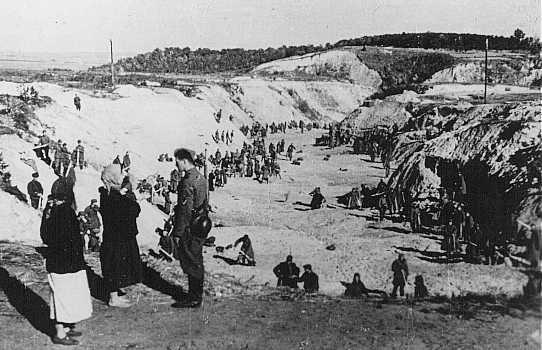 <p>Un membre d'un Einsatzgruppe (unité mobile d'extermination) parle avec deux femmes non identifiées au sommet du ravin de Babi Yar où 33 000 Juifs furent massacrés les 29 et 30 septembre 1941. Des prisonniers de guerre soviétiques dans le ravin nivellent la terre sur le charnier. On avait fait sauter les parois du ravin à la dynamite. Kiev, Union soviétique, automne 1941.</p>