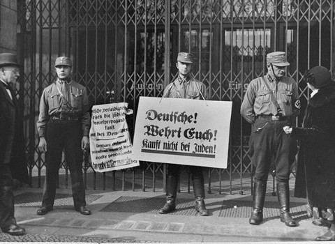 "<p>Members of the Storm Troopers (SA), with <a href=""/narrative/102"">boycott</a> signs, block the entrance to a Jewish-owned shop. One of the signs exhorts: ""Germans! Defend yourselves! Don't buy from Jews!"" Berlin, Germany, April 1, 1933.</p>"