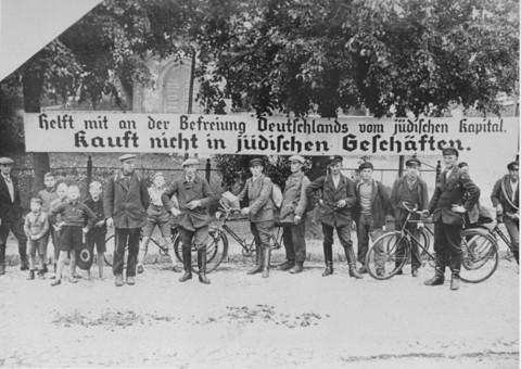 """<p>Cartaz usado durante o boicote anti-semita: """"Ajudem a libertar a Alemanha do dinheiro judeu. Não comprem em lojas de judeus."""" Alemanha, 1933.</p>"""