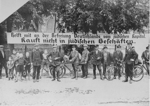 "<p>Tanda yang digunakan selama boikot anti-Yahudi: ""Bantu bebaskan Jerman dari modal Yahudi. Jangan membeli dari toko Yahudi."" Jerman, 1933.</p>"