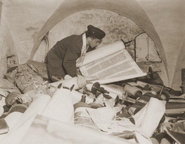 In the building of the former Nazi Institute for the Investigation of the Jewish Question, a US chaplain examines the Torah scrolls confiscated by Einsatzstab Rosenberg.