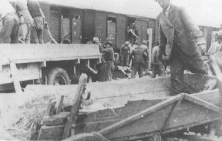 <p>Romaníes (gitanos) retiran los cuerpos del tren de la muerte Iasi-Calarasi en la parada de Tirgu-Frumos. Dos trenes partieron de Iasi en junio de 1930 con sobrevivientes del pogromo que tuvo lugar en Iasi el 28 y 29 de junio. Cientos de judíos murieron en los vagones superpoblados y sin ventilación en medio del calor del verano. Rumania, 1 de julio de 1941.</p>