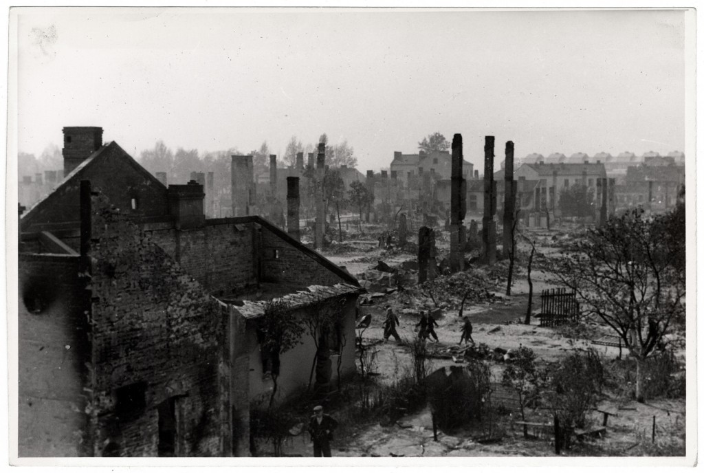 Poles walk among the ruins of besieged Warsaw. [LCID: 47270]